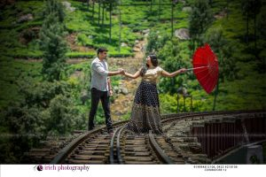 Couple Posing In rail track with umbrella